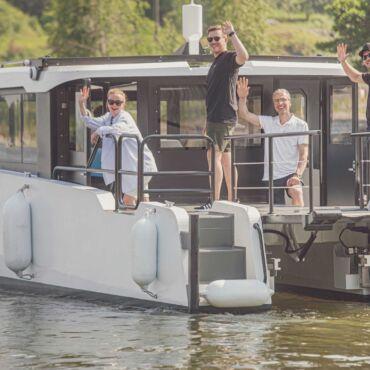 Vesillä valkoinen matala vene, kannella neljä ihmistä, kolme miestä ja nainen, vilkuttavat kameralle. Aurinkoinen päivä, kesä