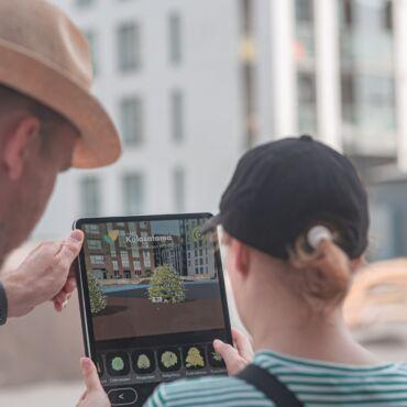 Mies ja nainen osoittavat iPadilla kerrostaloa, ruudulla piirrosnäkymä talosta. Molemmat selin kameraan, valoisaa, kesä.