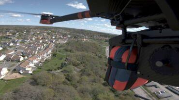 Drone ilmassa, kuljettaa punaista pakettia, kuvattu ilmassa. Alapuolella talojen kattoja, vehreää.