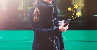 Nainen seisoo ratikan edessä ja puhelimeen tulee viesti, koska hän on älykkäässä kaupunginosassa.